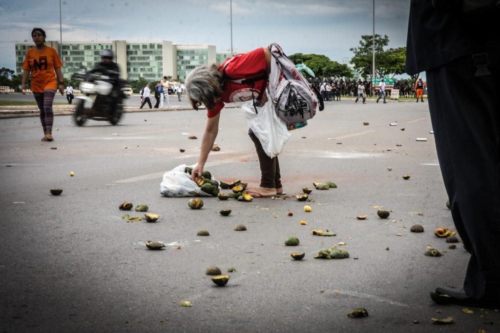No meio da confusão, mulher aproveitou para catar o que sobrou de uma caixa de pequi atirada pelos manifestantes contra os policiais. Foto por: Fábio Bispo